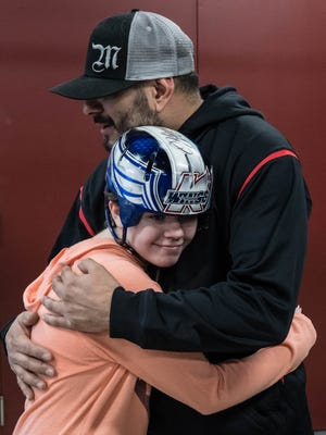 "Abigail ""Abbie"" Kopf hugs Hot Rods and Handlebars General Manager Art Solis Tuesday after the shop presented her with a custom Batman helmet in 2016. Kopf is one of two survivors from a random shooting spree Feb. 20 in Kalamazoo County."