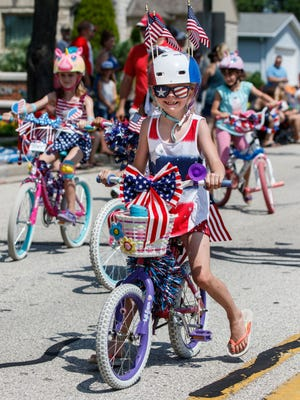 Mia Knetter, 7, of Grafton, rides her decorated bicycle in the Grafton Independence Day parade on Saturday, June 30, 2018.