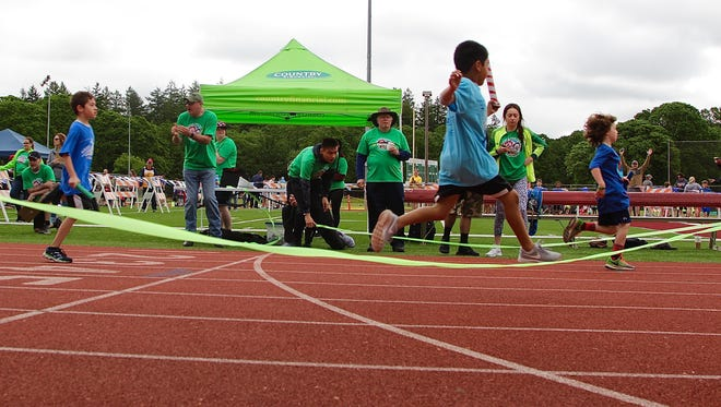 First-grade boys cross the finish line as part of the 43rd Annual Country Financial Kids Relays at the Willamette University McCulloch Stadium on Saturday, May 20, 2017.