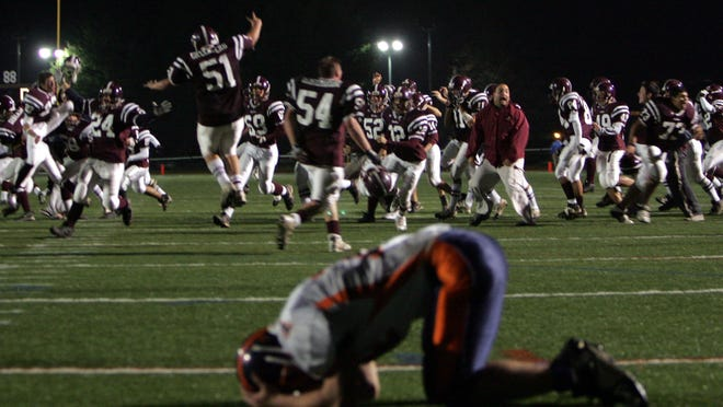 Harrison High School's football team celebrates its 13-7 overtime victory over Horace Greeley in the Section 1 Class A Championship at Mahopac High School on Nov. 6, 2005. Greeley's Franke Holiber lays dejected in the end zone.