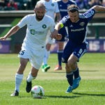 Saint Louis FC defender Brandon Barklage and Louisville City FC forward Matt Fondy and battle for the ball during last Saturday's opener.