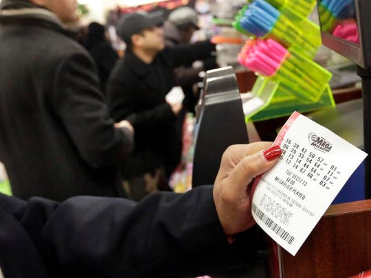 A woman plays the Mega Millions lottery at a shop in New York's Penn Station, Tuesday, Dec. 17, 2013. The Mega Millions jackpot soared to $586 million on Monday, still short of the $656 million U.S. record set in a March 2012 drawing.  (AP Photo/Richard Drew)