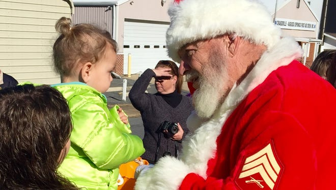 Bethan Black, 2, accepts a candy cane from Santa on Dec. 5, 2015.