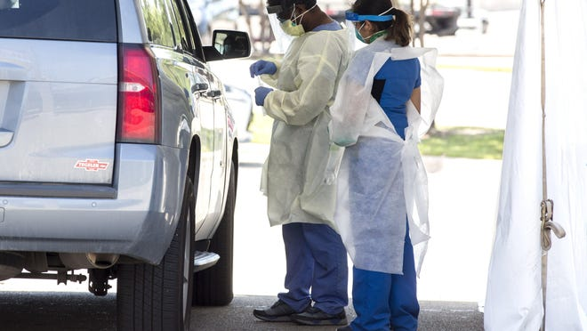 Medical staff prepare to swab a patient for coronavirus in a drive-through testing center at CommUnityCare Walk-in Clinic near East 41st Street in Austin on April 29.