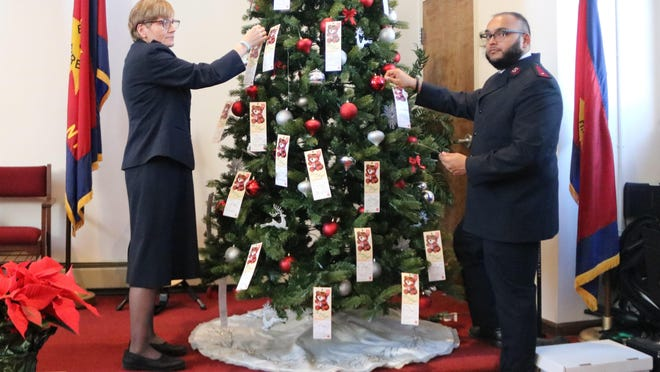 Captain Kelly Ross and Lt. Nereus Mogaria  hang tags with children's holiday wishes on the Angel Tree at the Port Jervis Salvation Army.