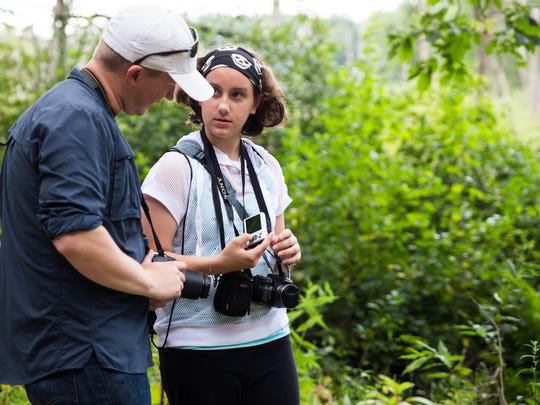 Paige Dittenbar, right, shows off some of her pictures to Parks in Focus Program Manager Bret Muter during their trip to the Ott Biological Preserve on Monday.