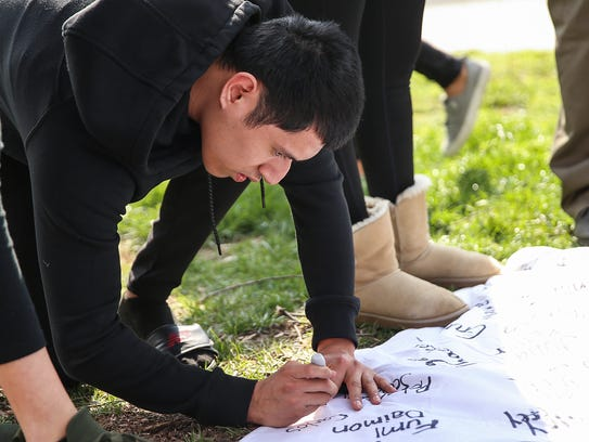 Students at DePauw University sign a banner on April