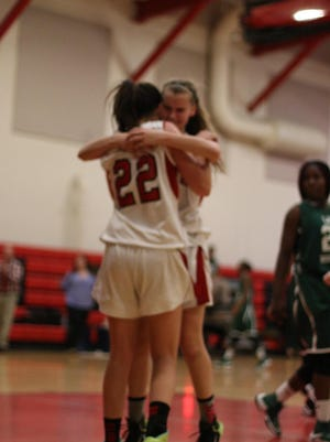 Taylor Rondanini (22) is hugged by teammate Melissa Herforth after scoring her 1,000th point.