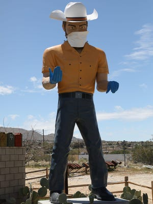 A cowboy statue is adorned with a mask in Joshua Tree.
