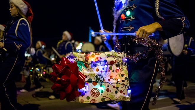 A member of the St. Clair High School Marching Band plays a drum decorated as a present during the St. Clair Lighted Santa Parade.