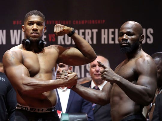 Britain's Heavyweight Champion Anthony Joshua, left, and challenger Carlos Takam pose during the weigh-in at Motorpoint Arena in Cardiff, Wales, Friday, Oct. 27, 2017. Joshua will take on Takam in a world title fight in Cardiff on Saturday. (Nick Potts/PA via AP)