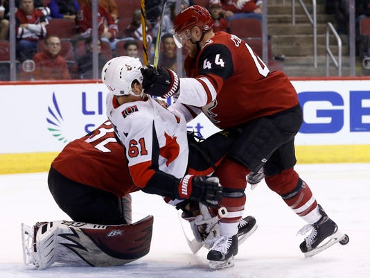 Arizona Coyotes defenseman Kevin Connauton (44) sends Ottawa Senators right wing Mark Stone (61) to the ice as they collide with Coyotes goaltender Antti Raanta, left, during the first period of an NHL hockey game Saturday, March 3, 2018, in Glendale, Ariz. (AP Photo/Ross D. Franklin)
