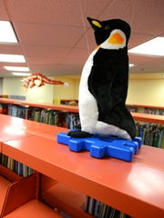 Stuffed animals are placed above the stacks in the children's area to help children find books of a related topic at the Salem Public Library.