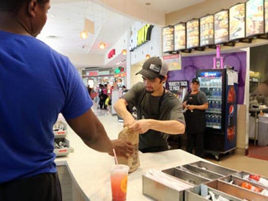 Rob Ozuna, 19, of White Plains, serves a customer July
