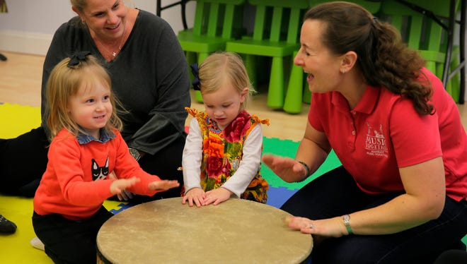 Amanda Munice (right) plays a drum with Amelia Dilworth (left), 2, West Long Branch, and Maddie Murphy, 21 months, Rumson, at Coco Beans Play Cafe in Tinton Falls Monday, January 18, 2016.   Maddie's mother Darryn Murphy looks on.  Munice is the owner of Manda's Music Together, a music education/appreciation program for kids and families.