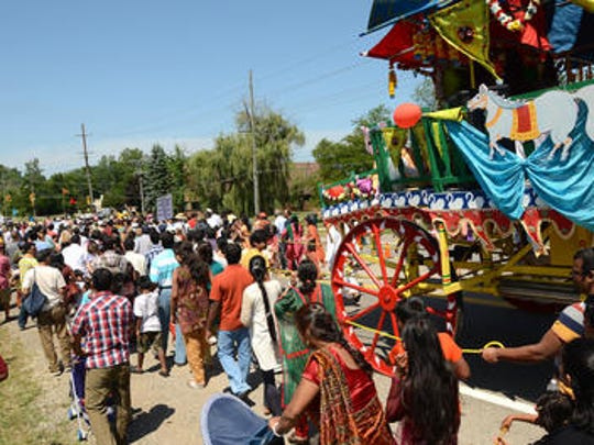 Hundreds of festival-goers join in pulling the chariot by ropes, for as great or as little distance as they care to go.