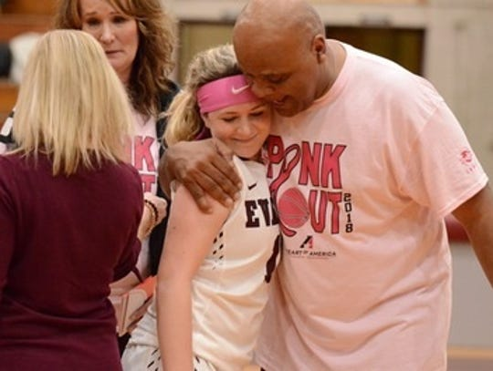 Evangel's Leon Neal hugs a player during senior night.