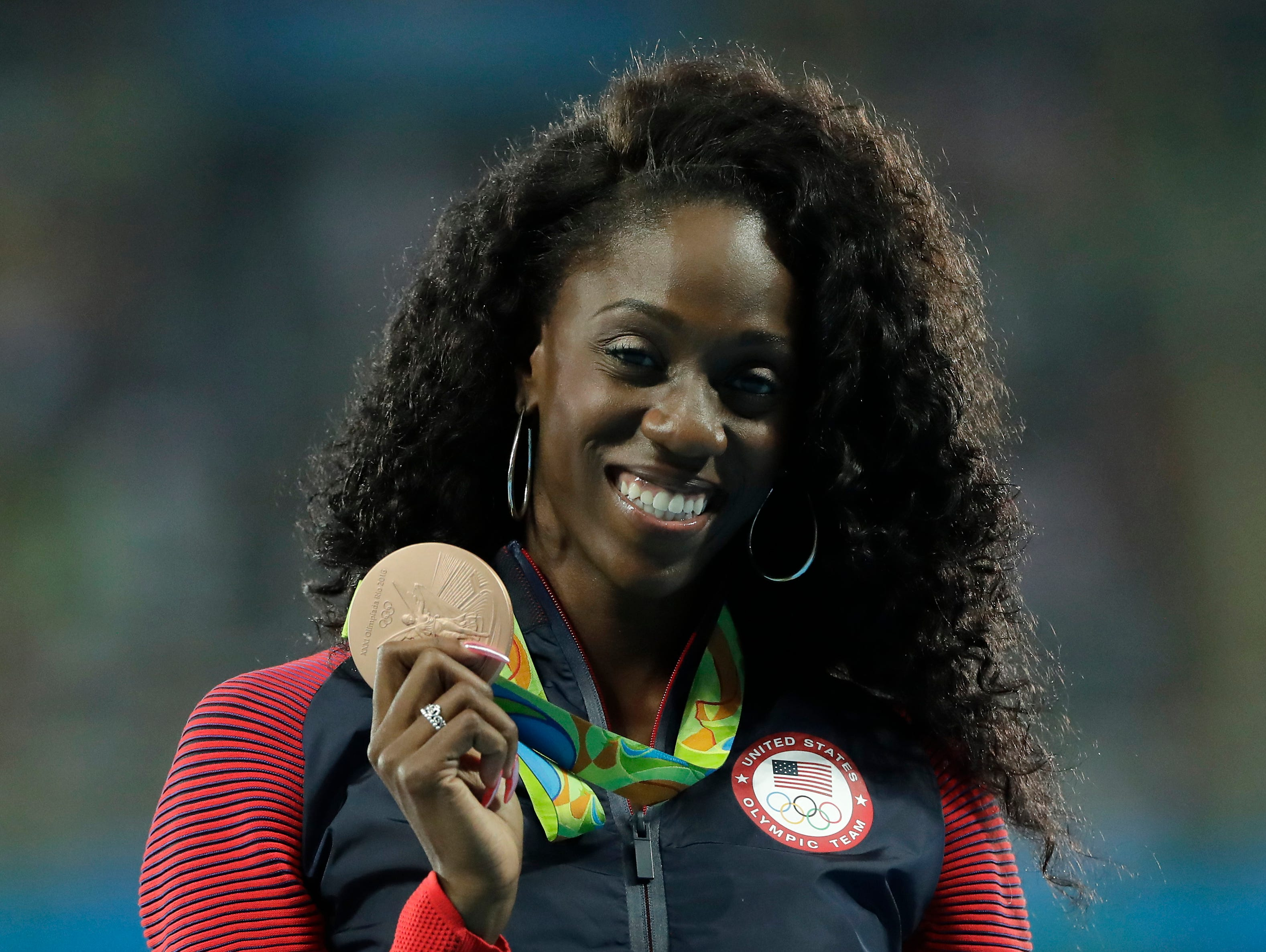 United States' Ashley Spencer shows off her bronze medal during the medal ceremony for the women's 400-meter hurdles race during the athletics competitions of the 2016 Summer Olympics at the Olympic stadium in Rio de Janeiro, Brazil.