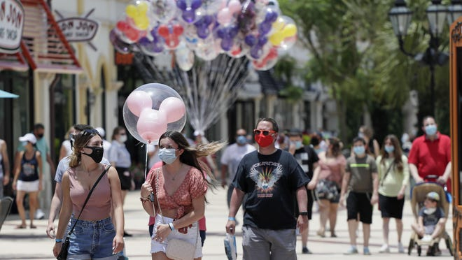 Guests stroll through the Disney Springs shopping, dining and entertainment complex in Lake Buena Vista on June 16. The Magic Kingdom and Animal Kingdom will reopen on Saturday.