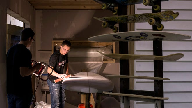 "Grant Fowler, 16, sands his surfboard with the assistance of classmate Steven Zwiez, 16, during their CTE Advanced Woodworking class on Tuesday, December 19th, 2017 at Eisenhower High School in Shelby Township. The students are able to create the longboards, paddle boards, skateboards and surfboards through the tech education program titled ""Gone Boarding."" (Brittany Greeson, Special to the Free Press)"