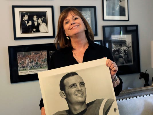 In this Wednesday, July 26, 2017 photo, Lise Hudson poses with photos of her husband, Jim Hudson, who played football for the University of Texas and the New York Jets in the 1960's, at her home in Austin, Texas. After his death, researchers found that Hudson suffered from stage IV chronic traumatic encephalopathy, the highest level of the brain disease. (AP Photo/Eric Gay)