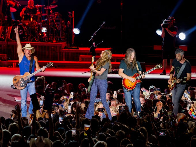 Kenny Chesney (left) reacts while playing on June 23,