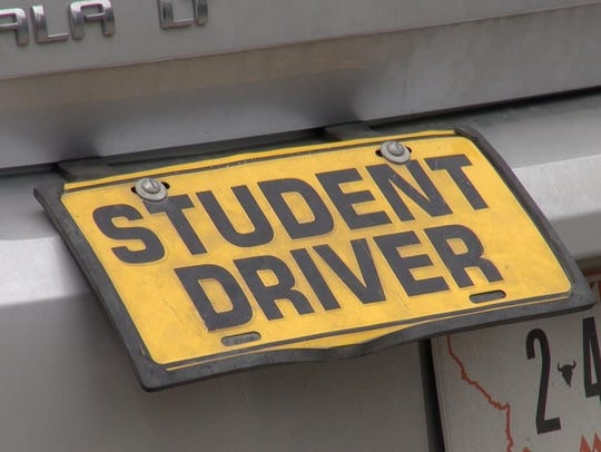 A student driver sign is attached to a car used for