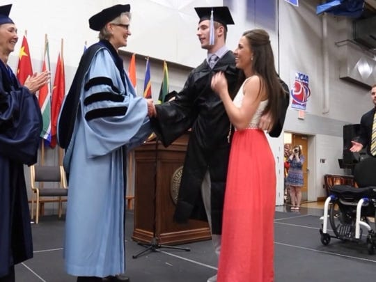 Chris Norton, paralyzed by a football injury five years ago, walked across the stage during graduation at Luther College Sunday.