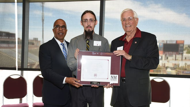 Derek Brown, center, was recognized Friday, May 11 as the spring 2018 Outstanding Graduate for the New Mexico State University College of Education. NMSU College of Education Dean Donald Pope-Davis, left, and NMSU Chancellor Garrey Carruthers helped to present the award.
