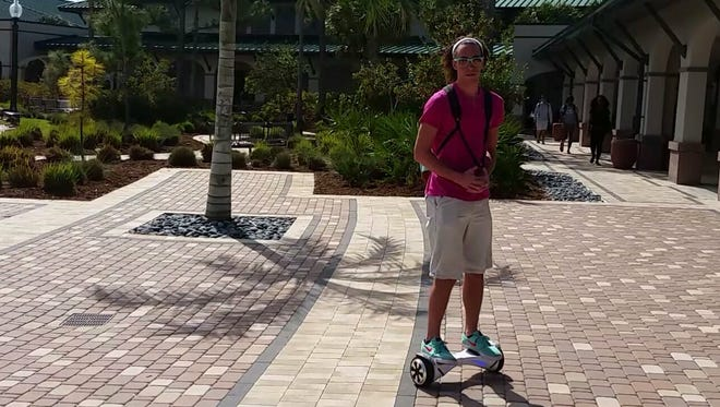 Florida Gulf Coast University student Anthony Rivers, 19, uses a hoverboard to get around the FGCU campus. The school has decided to ban the devices due to safety concerns.