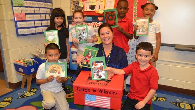 Students at Dane Barse Elementary School in Vineland recently designed Christmas Cards for veterans. Michele Thompson and some members of her first-grade class are pictured with the special box they used to collect the cards. which will be delivered to the veterans at the New Jersey Veterans Memorial Home in Vineland.