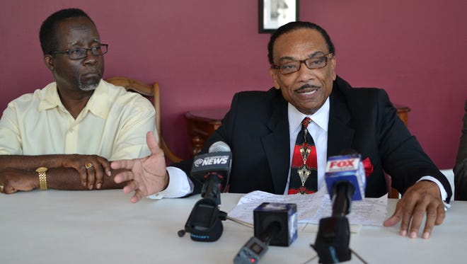 Norman Roberts, at left, watches as the Rev. Lewis Stewart speaks during a news conference Thursday. Stewart addressed recent national police shootings and the implications of those shootings on the Rochester community.