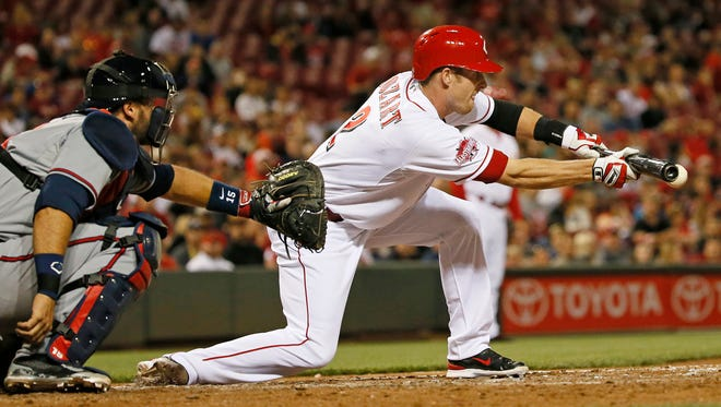 Reds shortstop Zack Cozart lays down a bunt during the bottom of the seventh inning Tuesday against the Braves.
