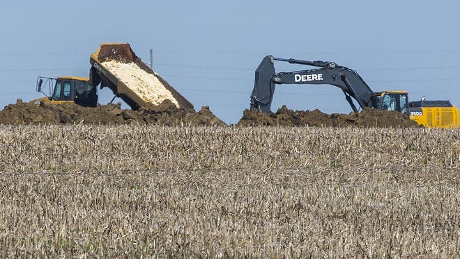 In this May 12 photo, dead chickens are buried in a farm field near Rose Acre Farms, near Winterset, Iowa, after the avian influenza virus was discovered there. (Rodney White/The Des Moines Register via AP)
