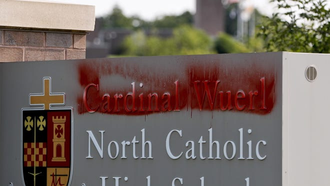 Paint covers the name of Cardinal Wuerl at Cardinal Wuerl North Catholic High School, on Monday, Aug. 20, 2018, in Cranberry Township, Pa. Wuerl, a Roman Catholic Cardinal, and the archbishop of Washington, D.C., has come under fire from revelations in the Pennsylvania grand jury report about his actions while bishop of Pittsburgh. (AP Photo/Keith Srakocic)