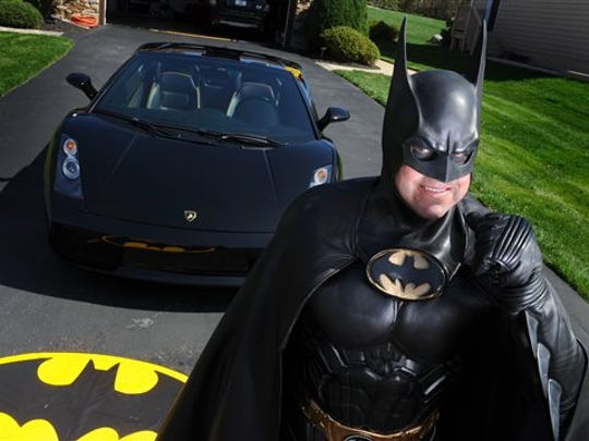 In this March 27, 2012, photo, Leonard Robinson, dressed as Batman, poses for a photo outside his home, in Owings Mills, Md. Authorities say, Robinson, known for visiting hospitalized children dressed in his Batman costume, died, Sunday, Aug. 16, 2015, in a crash on Interstate 70, in western Maryland. Police say Robinson was checking the engine of his Batmobile while standing in the fast lane of eastbound I-70 Sunday night when the car with hit by a Toyota Camry. The driver of the Camry wasn't injured.