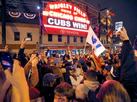 Chicago Cubs fans celebrate in front of Wrigley Field in Chicago on Wednesday, Nov. 2, 2016, after the Cubs defeated the Cleveland Indians 8-7 in Game 7 of the baseball World Series in Cleveland.