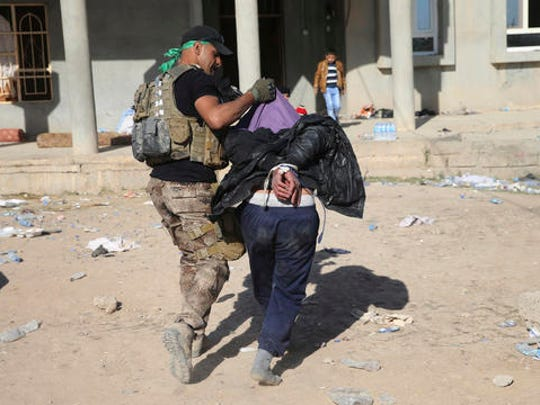 An Iraqi special forces soldier carries an alleged Islamic State group collaborator to inside a house where they gatherpeople to transfer them to refugee camps, in the Samah front line neighborhood, in Mosul, Iraq, Thursday, Nov. 24, 2016. Iraqi troops on Thursday drove Islamic State militants from three more neighborhoods in the northern city of Mosul, pushing toward the city center in a slow, street-to-street fight that's now in its sixth week, according to a senior Iraqi commander.