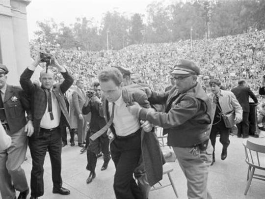 """FILE - In this Dec. 7, 1964 file photo, Mario Savio, leader of the Berkeley Free Speech Movement, is restrained by police as he walks on to the platform at the University of California's Greek Theater in Berkeley, Calif. The University of California, Berkeley has become a campus renowned for peace and openness where all viewpoints are welcome. It was anything but that on Wednesday night when violence and rioting forced the cancellation of a talk by right-wing provocateur Milo Yiannopoulos. A spokesman for the campus said it was """"not a proud night"""" for the birthplace of the Free Speech Movement."""