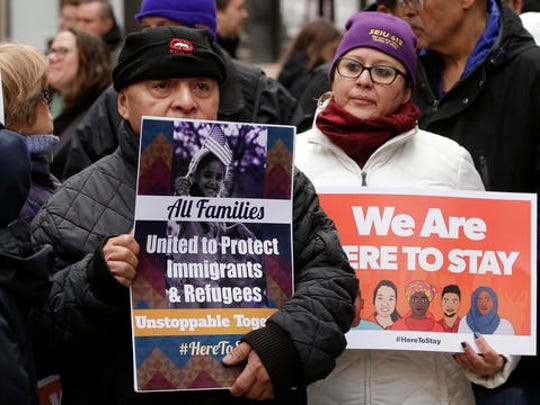 """Wilfredo Mendoza, of Boston, left, and Christina Villafranca, of Malden, Mass., right, displays a placards during a rally called """"We Will Persist,"""" Tuesday, Feb. 21, 2017, in Boston. According to organizers the rally was held to send a message to Republicans in Congress and the administration of President Donald Trump that they will continue to press for immigration rights and continued affordable healthcare coverage."""