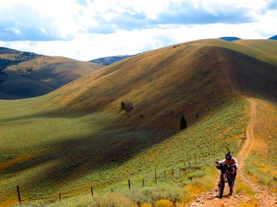 In this Aug. 15, 2014 photo provided by Scott Morris, Eszter Horanyi demonstrates hike-a-bike on the Continental Divide Trail in Montana.