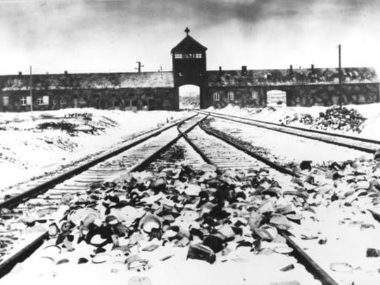 "FILE- This February/March 1945, file photo shows the entry to the concentration camp Auschwitz-Birkenau in Poland, with snow covered rail tracks leading to the camp.  The book, ""Human Rights After Hitler"" by British academic Dan Plesch, says Adolf Hitler was put on the United Nations War Crimes Commission's first list of war criminals in December 1944, but only after extensive debate and formal charges brought by Czechoslovakia. Plesch, who led the campaign for open access to the commission's archive, told The Associated Press on Tuesday, April 18, 2017, that the documents show ""the allies were prepared to indict Hitler as head of state, and this overturns a large part of what we thought we knew about him."""