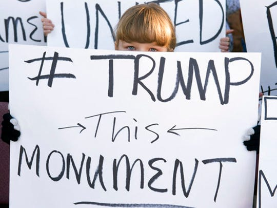 """FILE--In this Dec. 29, 2016, file photo, a young protester demonstrates with others against the new Bears Ear National Monument in Montecello, Utah. President Donald Trump signed an executive order Wednesday, April 26, 2017, directing his interior secretary to review the designation of dozens of national monuments on federal lands, as he singled out """"a massive federal land grab"""" by the Obama administration."""