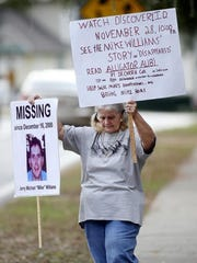Mike's mom Cheryl Williams held up one of his missing