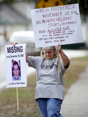 Mike's mom Cheryl Williams held up one of his missing person signs in front of Four Oaks Community Church on Sunday, November 20, 2011.