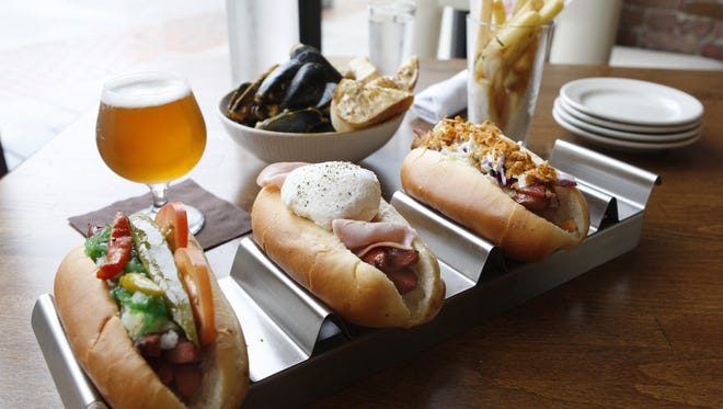 A photo of the Chicago hot dog, Croque Madame hot dog, and Trailer Park hot dog with a side of mussels charmoula and duck fat fries to be washed down with a la chouffe, a Belgian pale ale, from Senate, in Over-The-Rhine. T