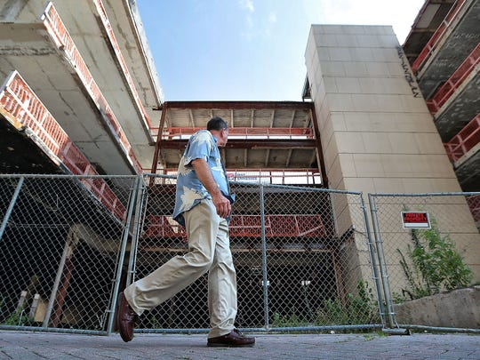 A pedestrian walks in front of the former Benchmark Hotel on Union Avenue. Nashville-area firm MNR Hospitality closedthe Benchmark in 2011 and gutted the structure.