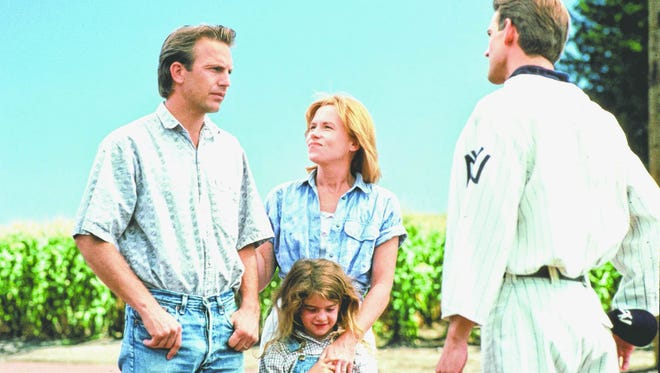 Kevin Costner, Amy Madigan, Gaby Hoffman and an unnamed baseball player in a scene from the 1989 motion picture Field of Dreams.