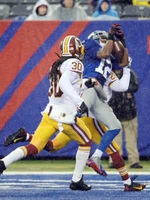 New York Giants wide receiver Jerrel Jernigan (12) catches a touchdown pass between Washington Redskins free safety E.J. Biggers (30) and cornerback Josh Wilson (26) at MetLife Stadium in East Rutherford, N.J. on Dec. 29, 2013.