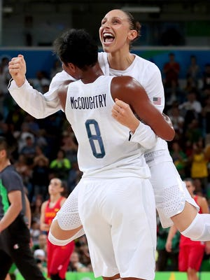 Americans Angel McCoughtry and Diana Taurasi celebrate after winning the women's basketball gold medal game against Spain.